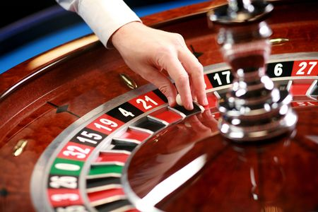 turning table: Casino roulette weel with mans hand  and little ball