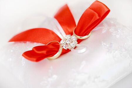 satiny: Gold wedding rings on a satiny pillow with red tapes Stock Photo