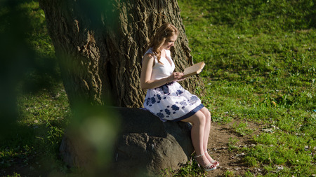 A girl with a book sitting near a tree photo
