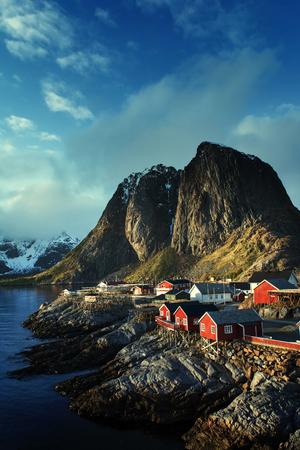 Rorbu on the background of rocks with ascending sun, Lofoten, Norway, Europa Stock Photo