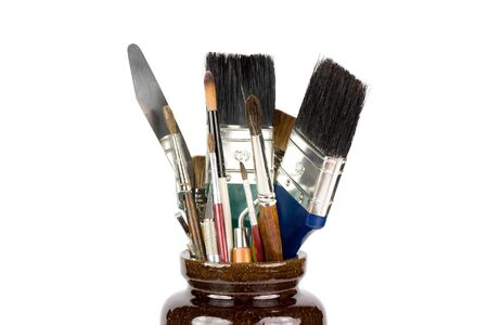 palette knife: Brown pot with brushes and palette knives.  Isolated on white. Stock Photo