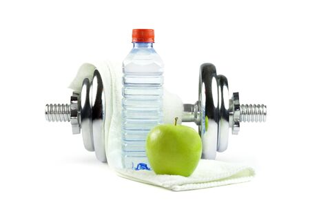 Metal dumbell with green apple, bottle of water and towel. Isolated on white Stock Photo
