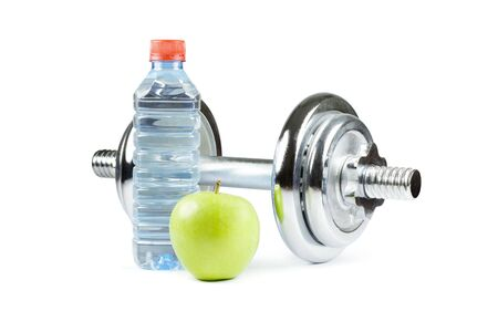 Metal dumbell with green apple and bottle of water. Isolated on white