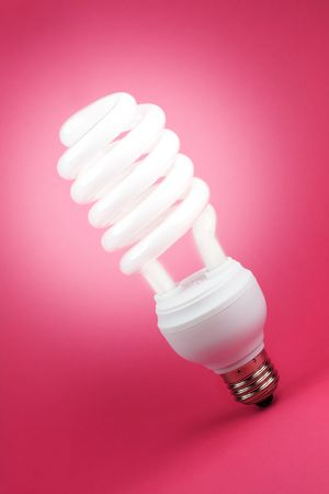 Turned on fluorescent light spiral bulb on pink background photo