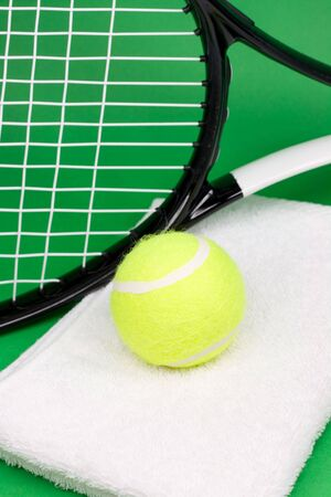Tennis ball, racket and towel on green background