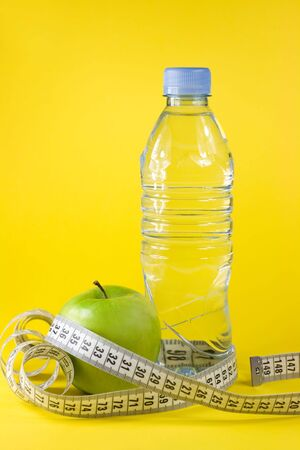 Green apple with centimeter and bottle on yellow background photo