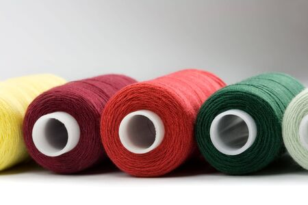 Colorful thread reels on white background photo