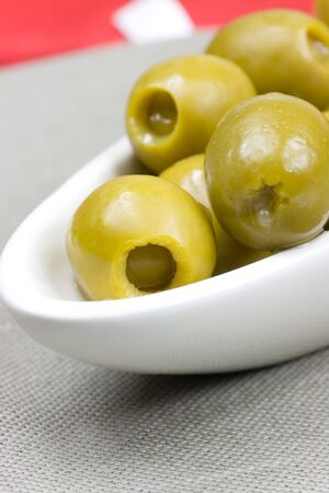 White plate with green olives