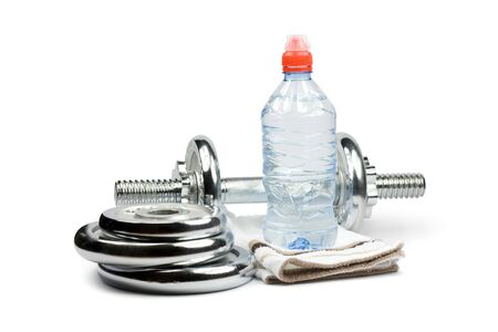 Metal dumbbell with bottle of water, towel and weights. Isolated on white