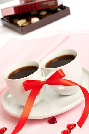 two coffee cups with red ribbon photo