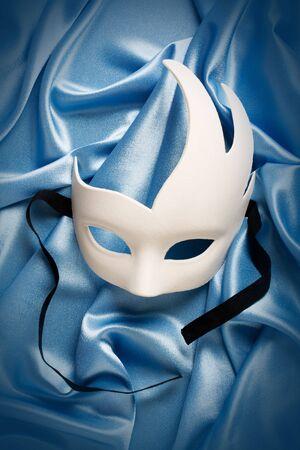 white carnival mask on blue silk