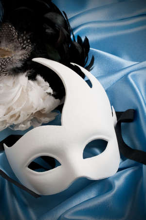white carnival mask on blue silk photo