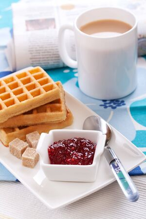 tasty waffles with jam, tea and newspaper photo