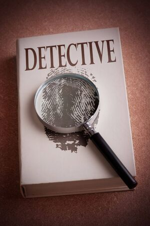 book with finger-print and magnifying glass photo