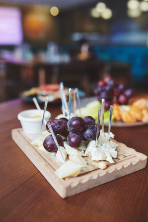 A plate of cheese, grape and sauce on wooden plate