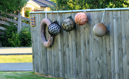fishing floats: Wooden fence decorated with fishing floats Stock Photo