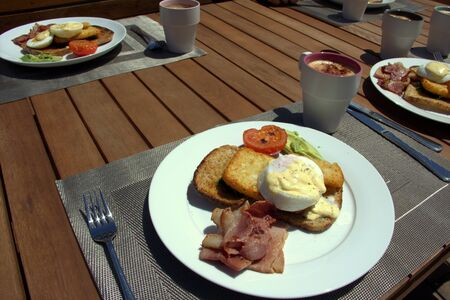 hashbrown: eggs Benedict and a cup of coffee for breakfast Stock Photo
