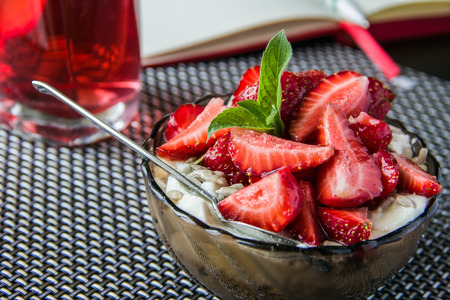 Porridge with fresh strawberries in a glass bowl of dark in the morning daylight photo