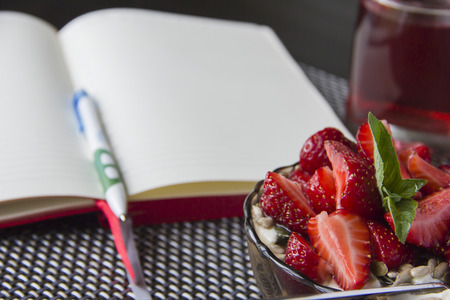 healthy product: Porridge with strawberries and open notebook to plan daily business during breakfast