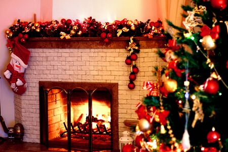 home decorated: Warm, bright, cozy fire burning fireplace in the home, decorated with Christmas lights and Christmas tree