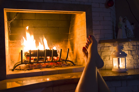 girl sitting: Female legs basking at home fireplace