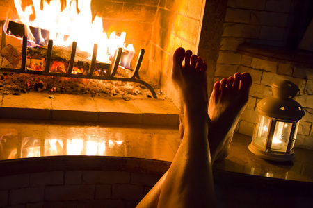 fireplace home: Female legs basking at home fireplace