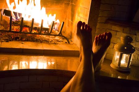 Piernas femeninas que toman el sol en la chimenea en casa