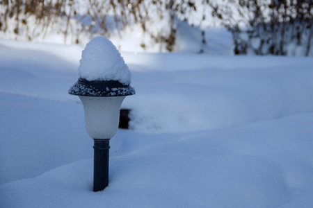 Solar Lantern in the winter garden in the middle of snow