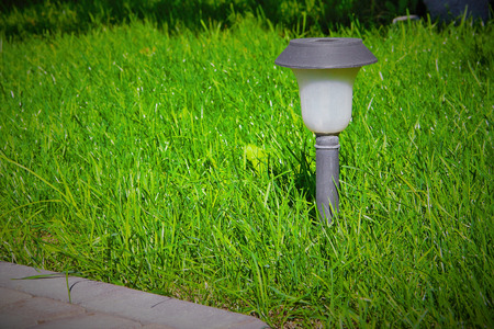photocell: Garden lighting - lights on the solar battery on a green lawn next to a paved path Stock Photo