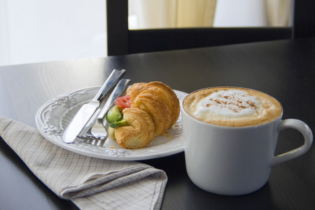 Coffee cup and fresh baked croissants on black background