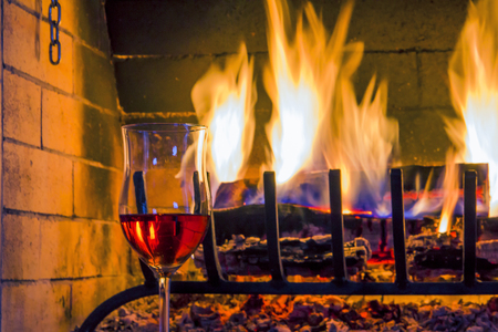 glass of wine around the open fire Stock Photo