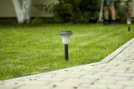 Solar Lantern is on the green lawn next to a paved garden path.