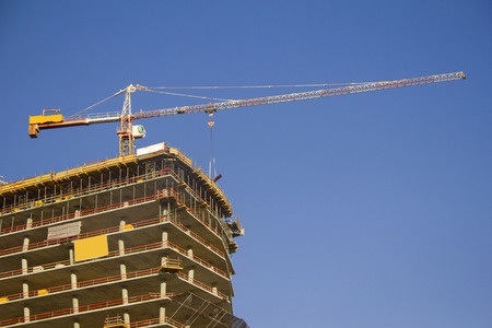 baffle: Building of a skyscraper with a tower crane Stock Photo
