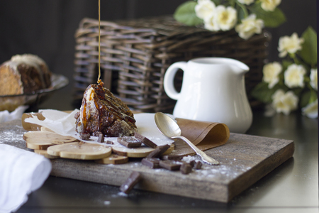 piece of chocolate cake with praline and caramel icing on a wooden surface, daylight, dark background, rustic style