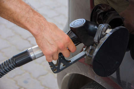 Man refueling a car tank with gasoline at a gas station Stock Photo