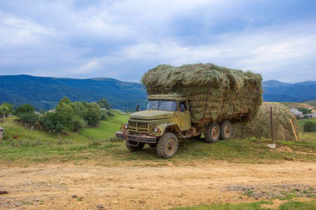 Old truck with hay in the background of a magnificent mountain landscape. Farming concept, preparation of livestock feed. Karachay-Cherkessia.