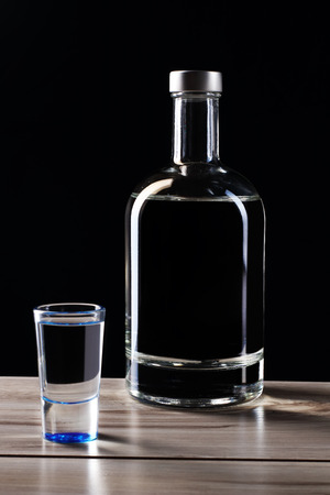 bottle of vodka with a glass on a black background