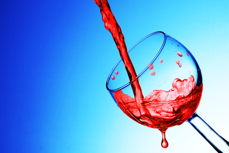 pouring wine into a glass on a blue background