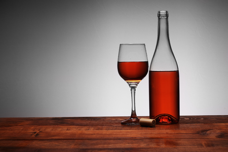 bottle of wine with poured goblet on a white background