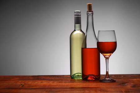 bottles of wine with a full cup on a white background Stock Photo