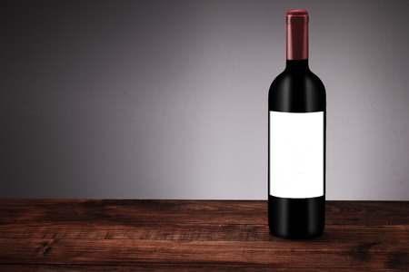 a bottle of red wine on boards and a white background