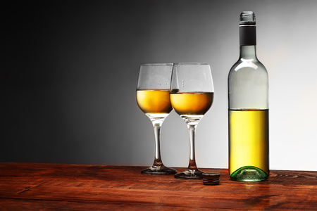 a bottle of wine with two full goblets on a white background