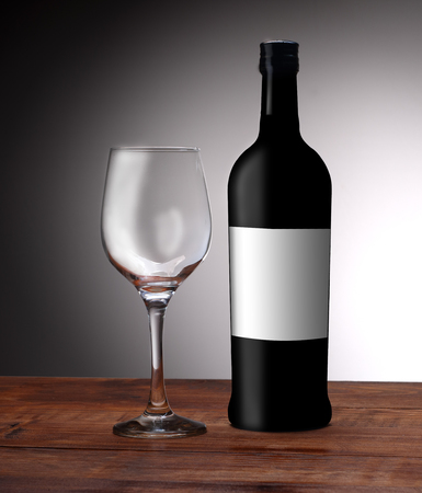 a bottle of wine with an empty glass on a white background Stock Photo