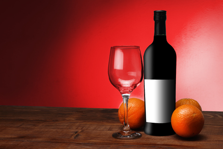 a bottle of wine with oranges and a glass