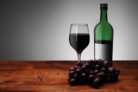 red wine with a glass and grapes on a white background