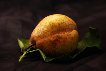 ripe pear on a leaf and a black background