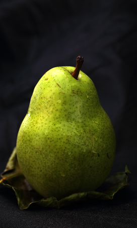 pear fruit on a leaf and a black background