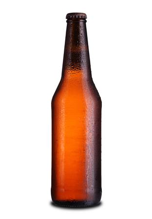 Botella llena de cerveza con gotas sobre un fondo blanco. Foto de archivo