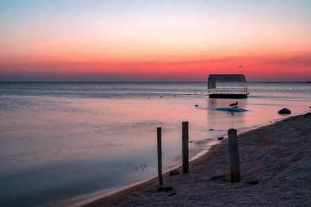 Beautiful pink gradient sunset on the shore of a deserted sea beach