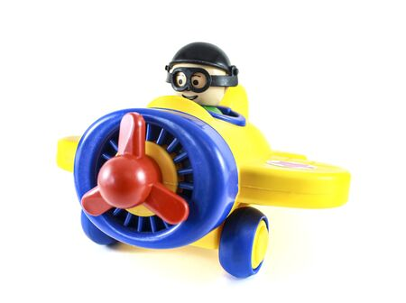 Toy airplane with a propeller with a pilot on a white background. Bright, multi-colored colors. Фото со стока